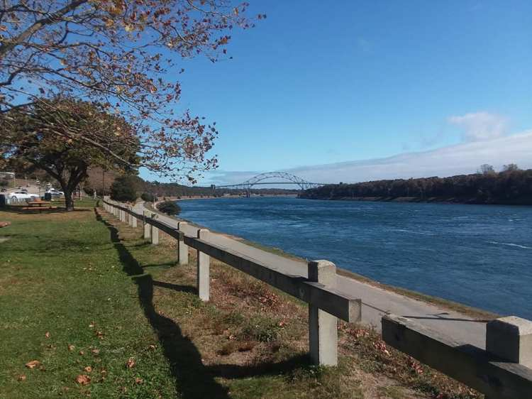 picture of a park next to the Cape Cod Canal, blue water, blue sky, with the Sagamore Bridge in the distance.