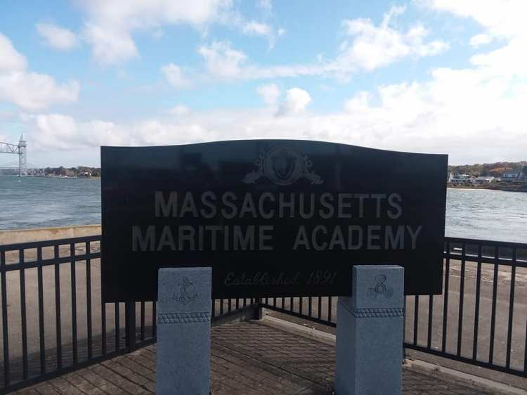 Picture of a black marble sign for the Massachusetts Maritime Academy, next to the Canal, with the railroad bridge in the distance.