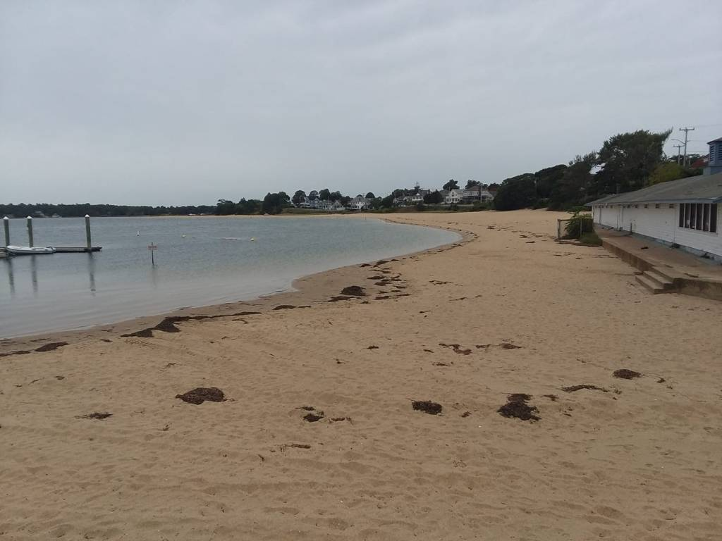 This is a picture of Onset Beach, taken on a cloudy day, it is in-between high tide and low tide, the old boathouse is to the right of the picture.