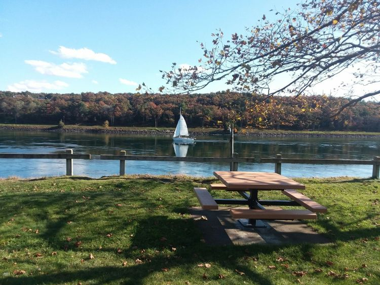 picture of a sail boat on the canal, a square, wooden picnic table and the fence along the park.