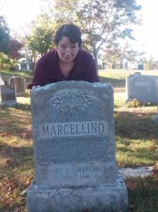woman standing behind parents headstone at a cemetary