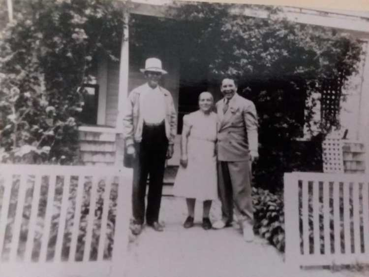 Picture of a tall man with a hat, a short woman and another man (my grandparents and my dad)