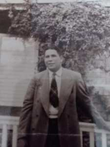 A young man in a suit holding a cigar