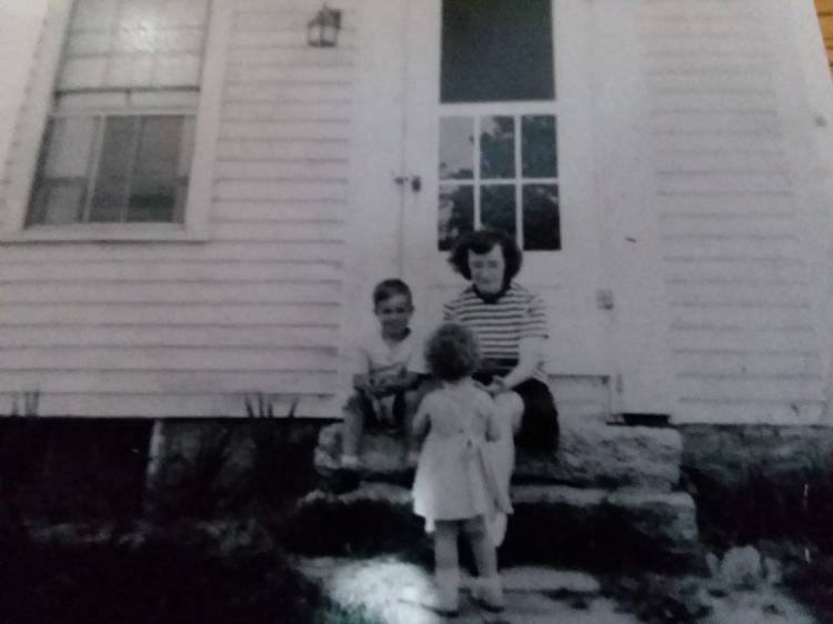 picture of a woman sitting on stone steps in front of an old house. A young boy sits next to her and a young girl stands facing her.