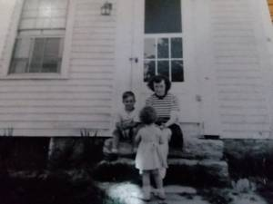 Woman and boy sitting on the steps of a house, toddler girl facing the woman