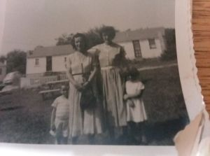 Two children and two women in the foreground of some beach cottages