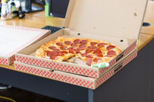 Picture of a pepperoni pizza in a box with other boxes on a table.