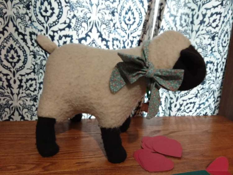 Picture of a stuffed sheep on a desk with red paper hearts in the foreground.