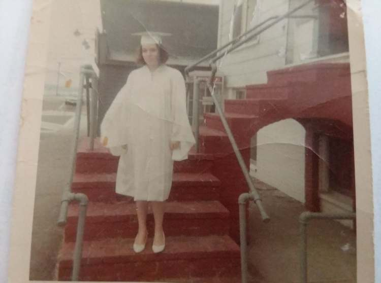 Old picture of a young girl in a white cap and gown for high school graduation.