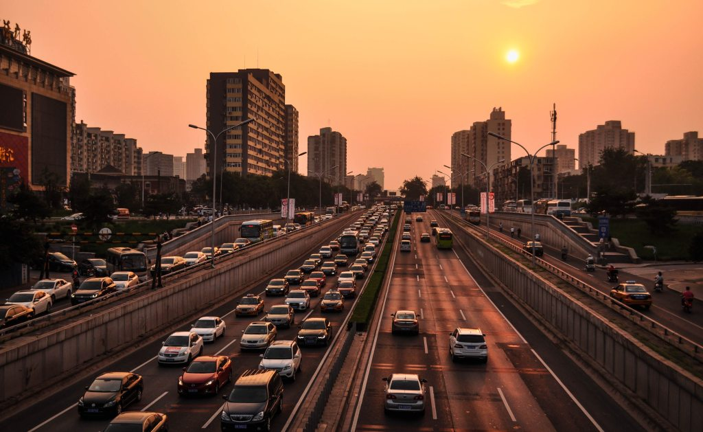 picture of heavy traffic  on a highway with on and off ramps, city in the background.