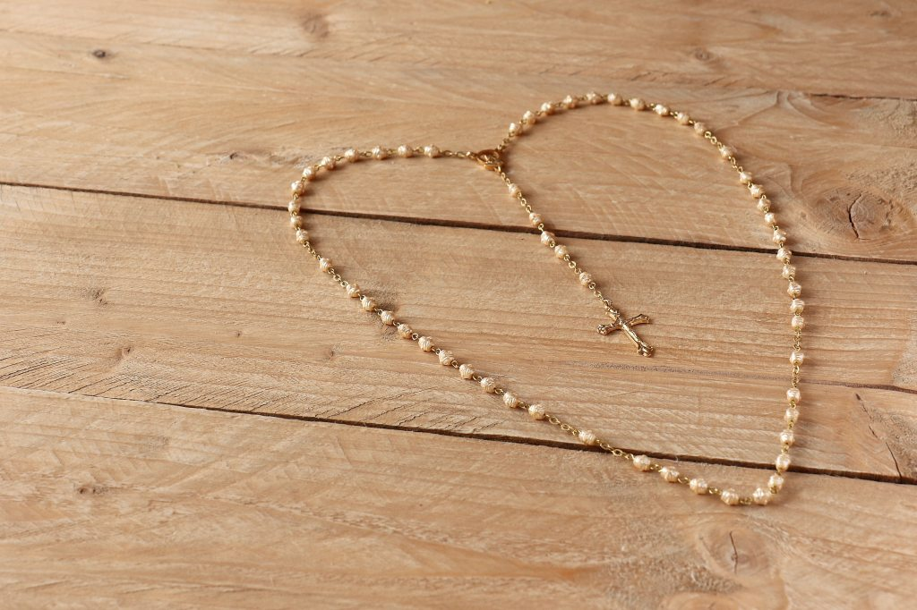 picture of a rosary, white beads, gold chain light colored wood background.