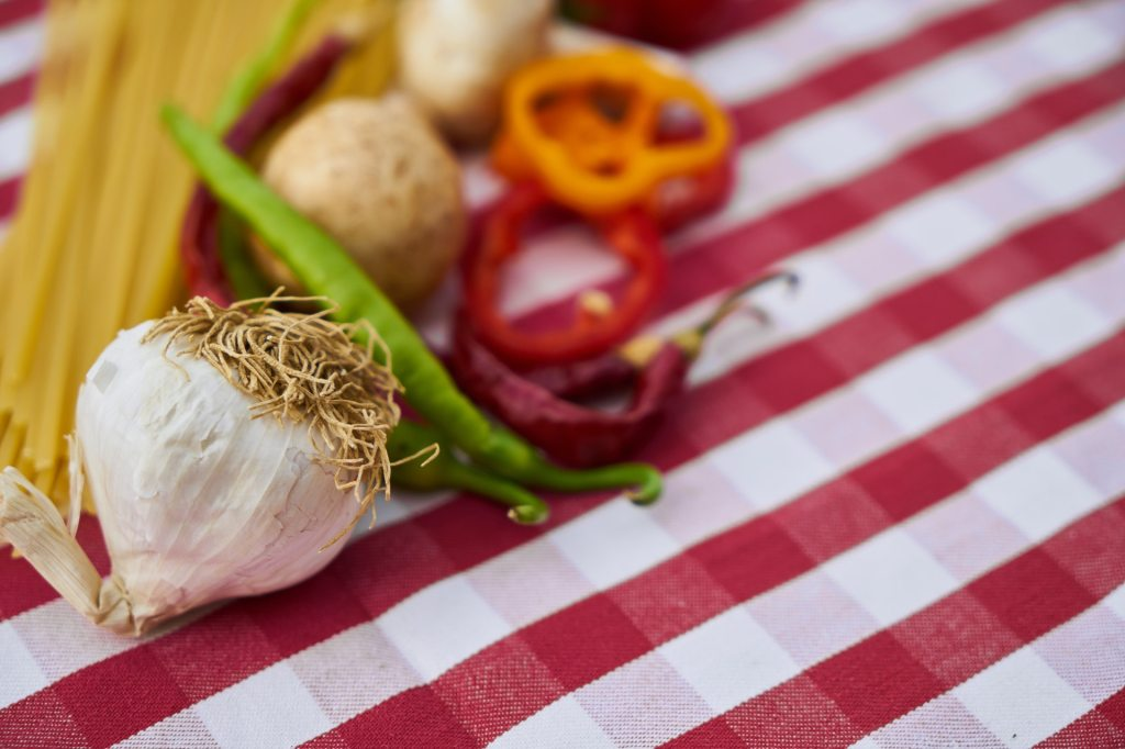 picture of garlic, red and green pepper chilis, mushrooms and pasta on red and white checked table cloth