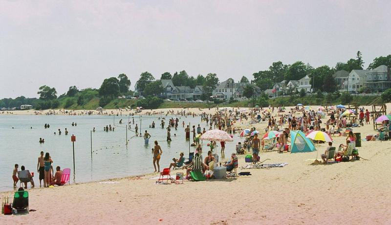 A picture of Onset beach in the summer, with people on the beach, umbrellas, lifeguard stands, etc.