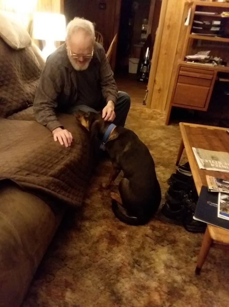 Picture of a man with a beard sitting on the couch petting a large black and tan dog.