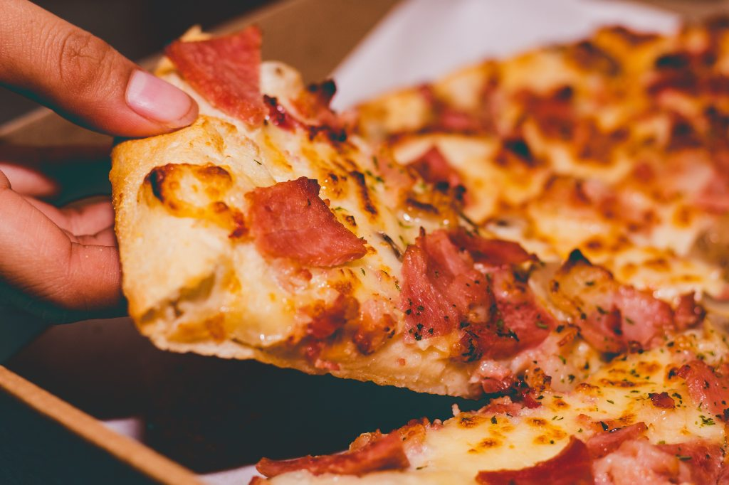 Picture of a person's hand  holding a slice of pizza.