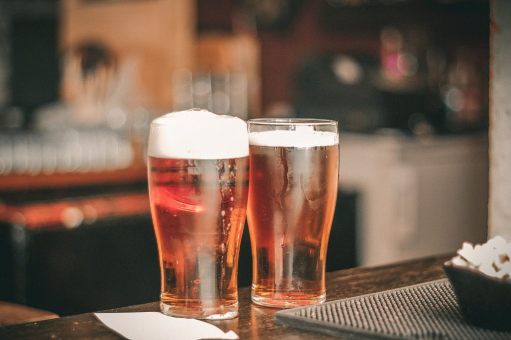 Picture of two pislner glasses on a bar