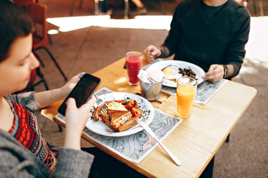 Picture of two people at a square table, one has a cell phone in hand.