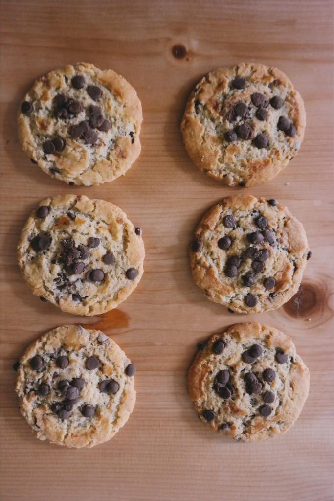 Picture of a half dozen chocolate chip cookies, lots of chips on a board
