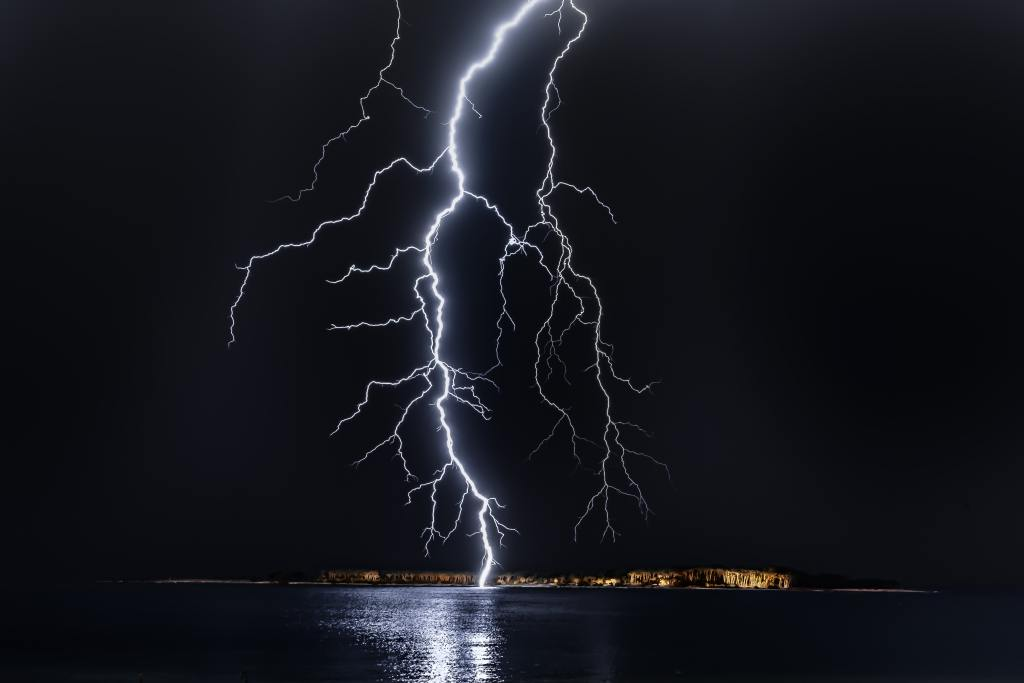 Picture of a lighting strike at night, dark sky, black water