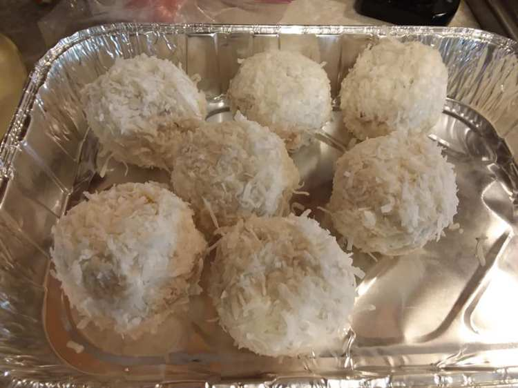 Picture of 7 snow ballcupcakes in a foil tray.