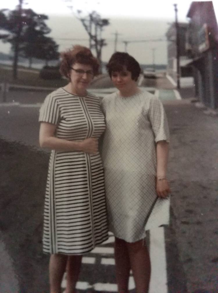 Picture of a woman and a teenager standing on a street.