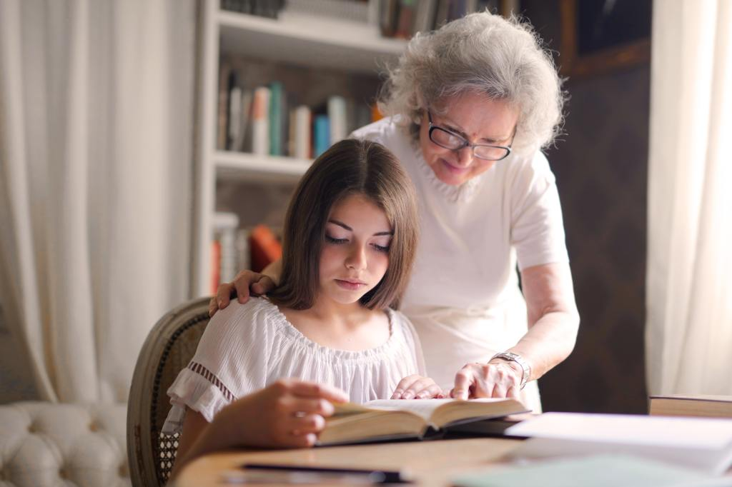 Picture of an older woman looking over the shoulder of a young girl looking at a book.