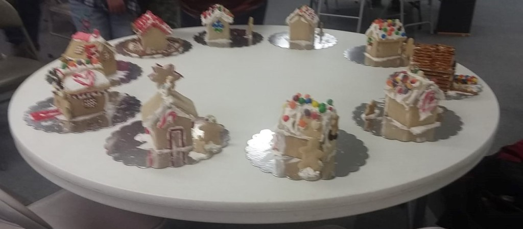 A white round table with10 gingerbread houses on it.