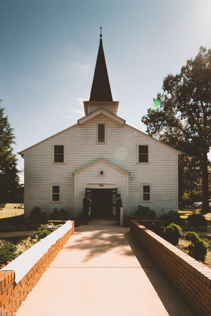 Picture of a white church building with the doors open and two groomsmen outside the doors.