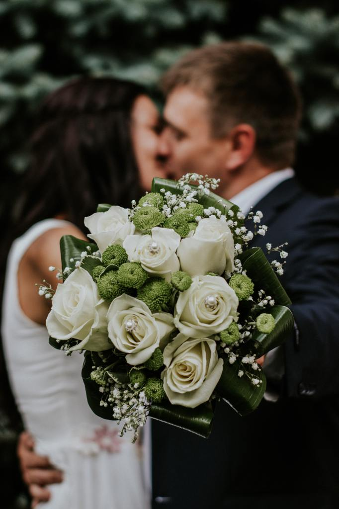 Picture of a bride and groom kissing, Bride's bouquet with white roses and with greens