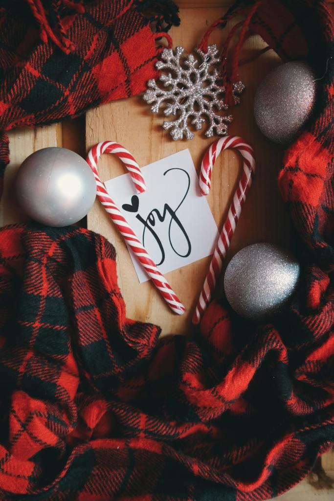 "Picture of Christmas decorations, ed and black flannel cloth and the word ""JOY"" in the center."