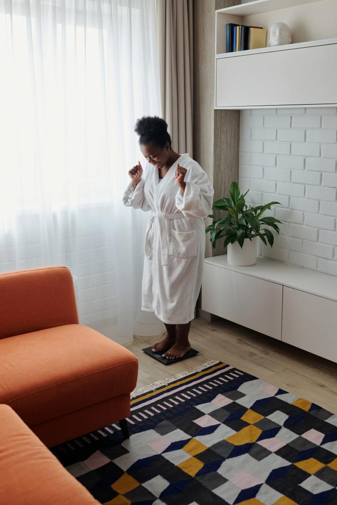 Picture of a woman on a scale she wears a white robe and her hands are raised in  hope