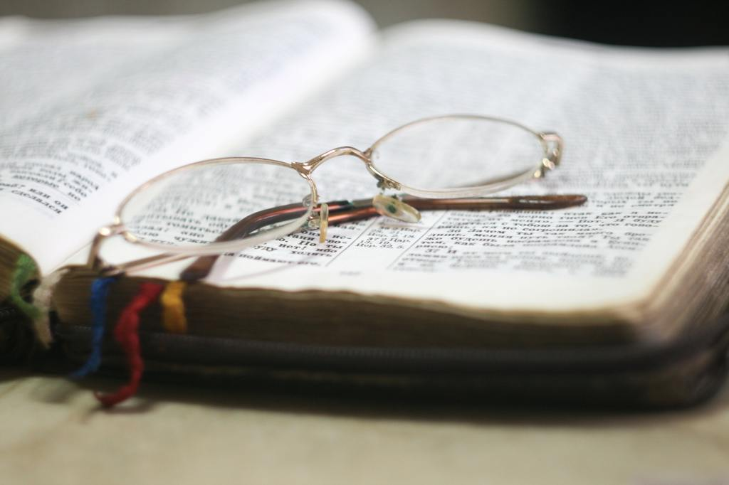 Picture of a bible with a pair of glasses on it.