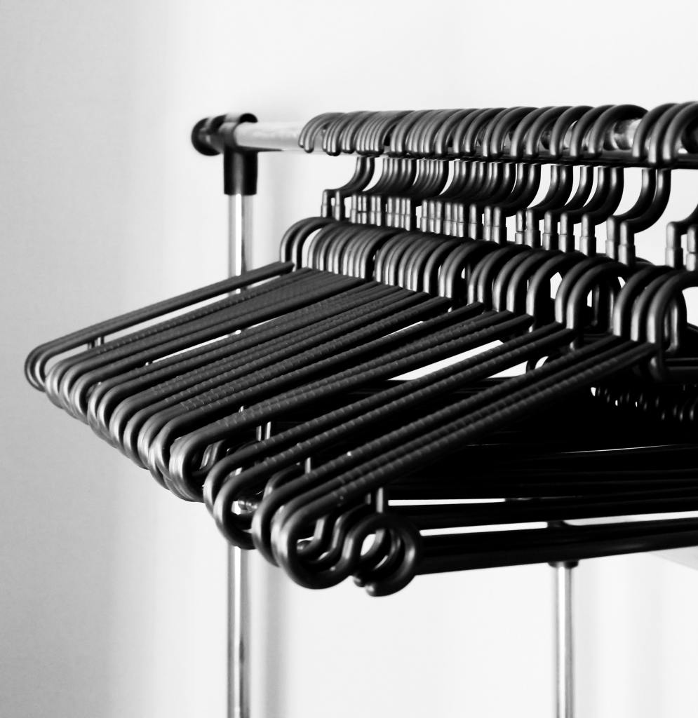 Black and white picture of a clothes rack with empty hangers.