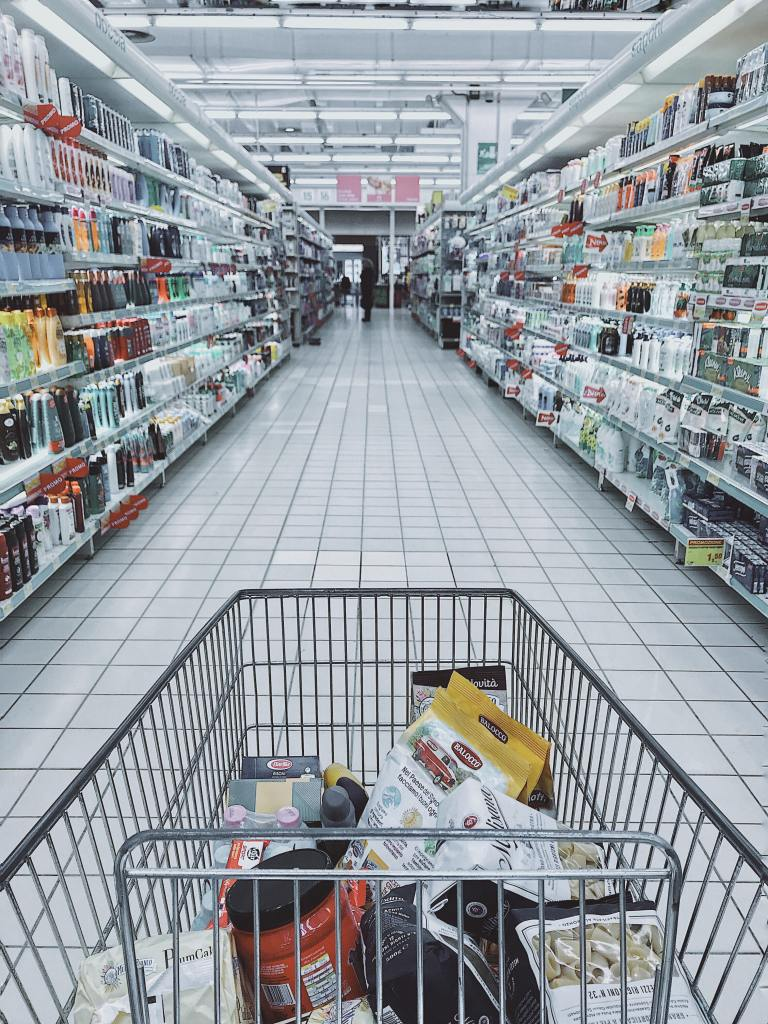 Picture of a grocery cart with some items in it, fcing an ailse with bottles and other items.