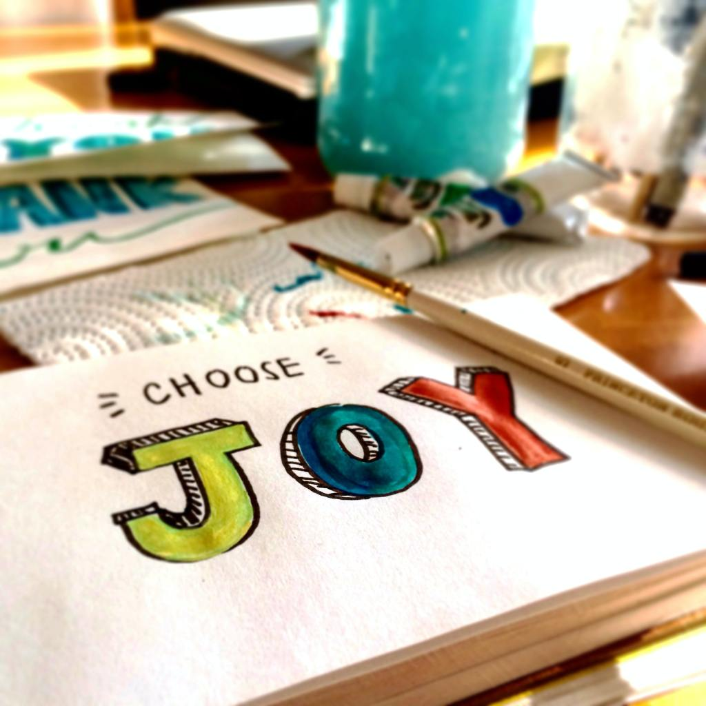 "Picture of a painted sign that says ""Chose JOY, with eh letters painted in Green, blue and red."