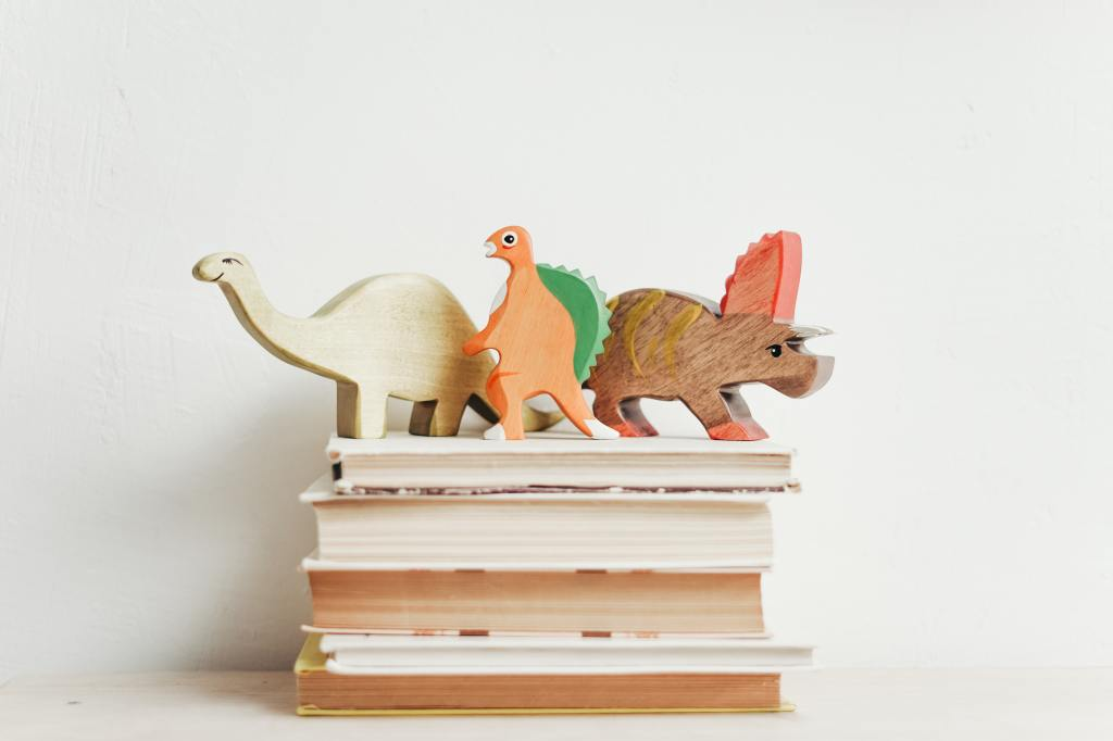 Picture of wooden toy dinosaurs on top of a stack of books.