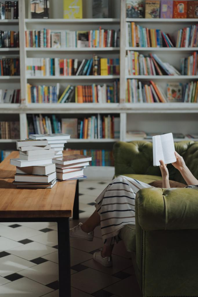 A picture of a wall of book cases and books. Stacks of books on a brown table and a woman sitting on a couch reading a book.