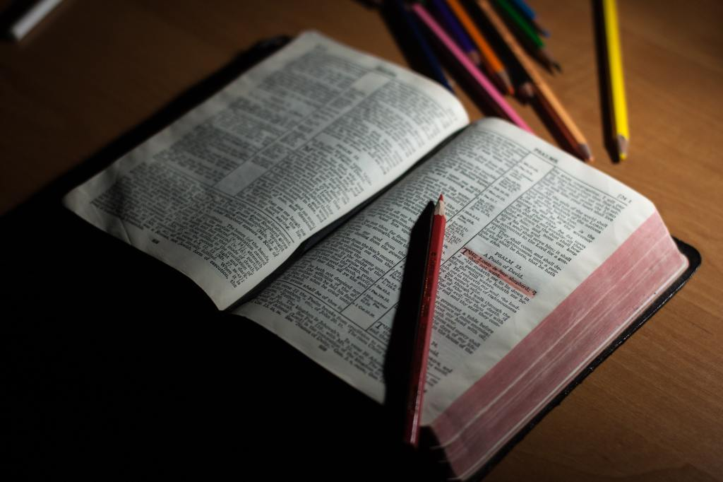 Picture of an open Bible with colored pencils in the background.