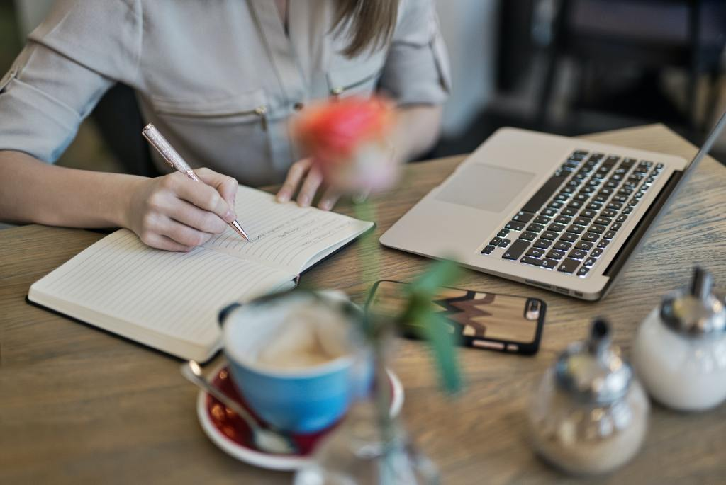Picture of a woman writing in a notebook. On the table in front are a laptop, cell phone, coffee cup and salt and pepper