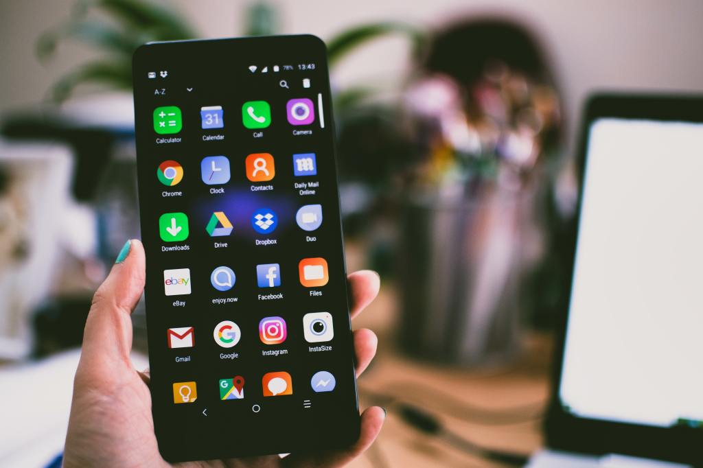 Picture of a hand holding a smart phone loaded with icons for apps