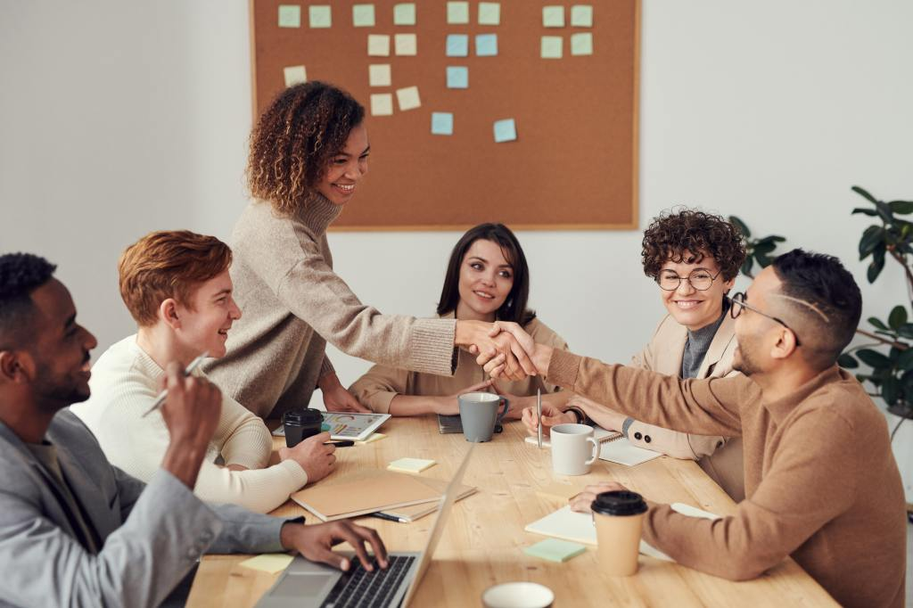 Picture of a diverse group of young people sitting at a table, a young woman and man shaking hands.