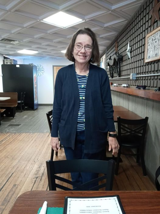 Picture of the author, dressed in blue and white, standing in a restuarant.