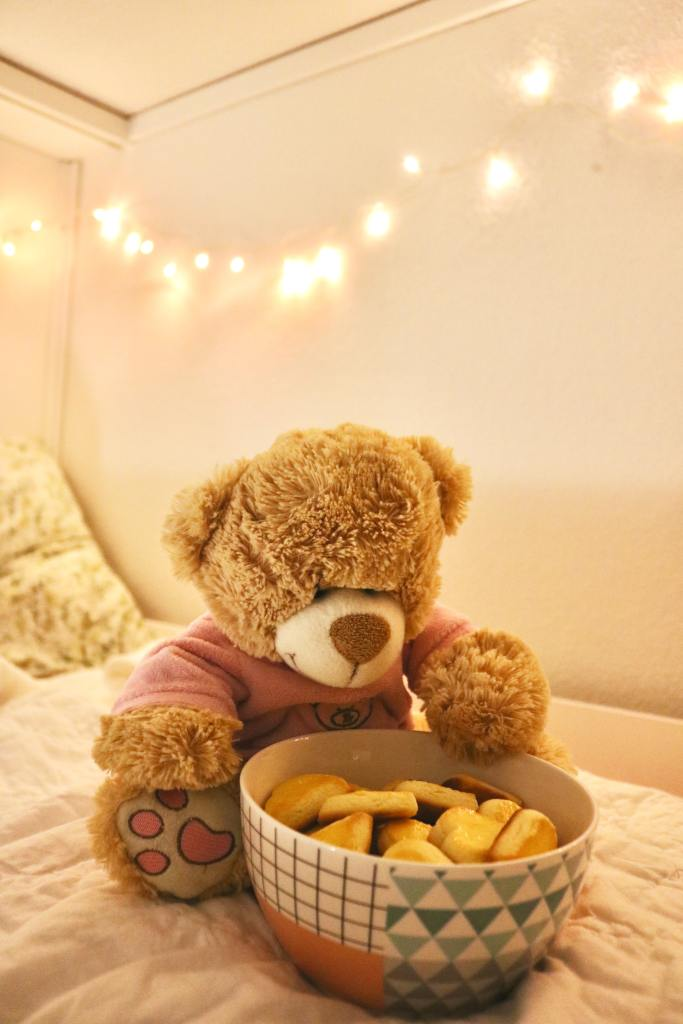 Picture of a teddy bear on a bed, with a bowl of heart shaped cookies.
