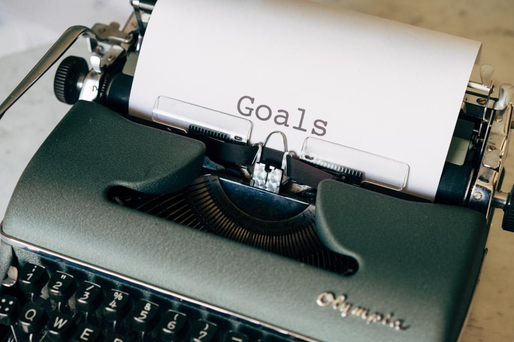 """Picture of an old fashioned typwriter with a paper inserted and the word """"Goals"""" typed on the page."""